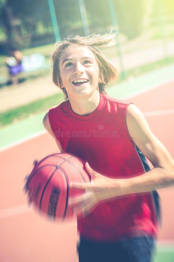 Begrepp för livsstil för tonåringar för lycklig tonåringlekbasket utomhus- sunt sportigt i vår- eller sommartid arkivbild