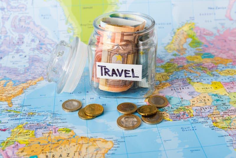 Begrepp för loppbudget Pengar sparade för semester i den glass kruset på översikt arkivfoton
