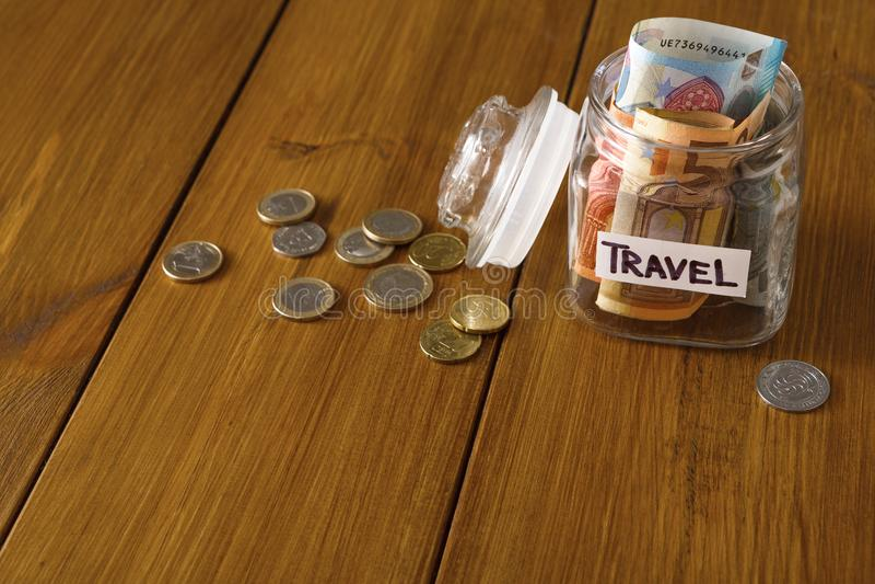 Begrepp för loppbudget Pengar sparade för semester i den glass kruset på översikt fotografering för bildbyråer