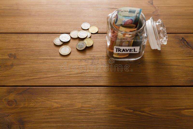 Begrepp för loppbudget Pengar sparade för semester i den glass kruset på översikt arkivbild
