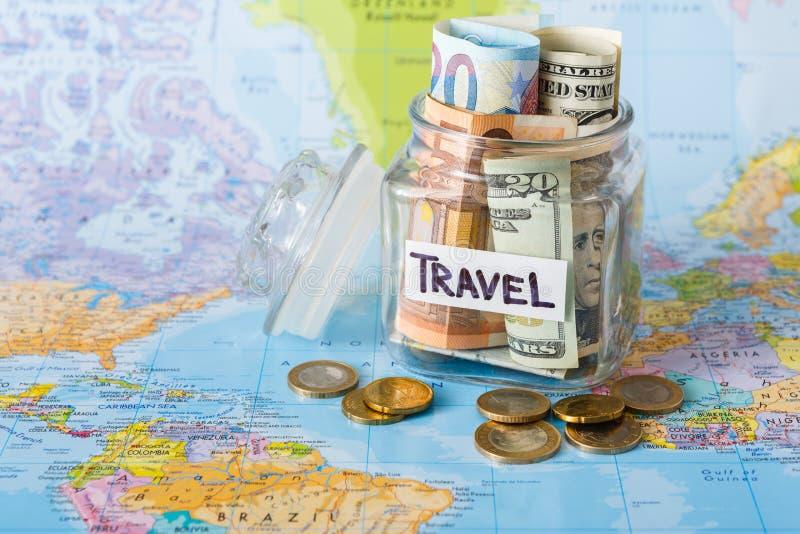 Begrepp för loppbudget Pengar sparade för semester i den glass kruset på översikt royaltyfri fotografi
