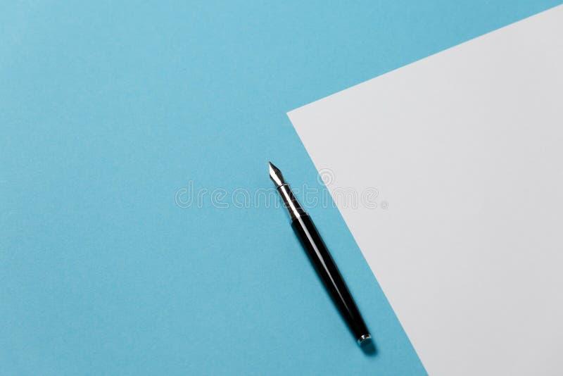 Begrepp för Minimalism för kreativitet för kontorsutrymme Pen Lies On ett tomt ark av papper på blåttyttersida, lekmanna- lägenhe royaltyfri fotografi