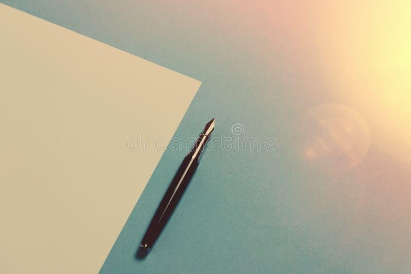 Begrepp för Minimalism för kreativitet för kontorsutrymme Pen Lies On ett tomt ark av papper på blåttyttersida, lekmanna- tonad b fotografering för bildbyråer
