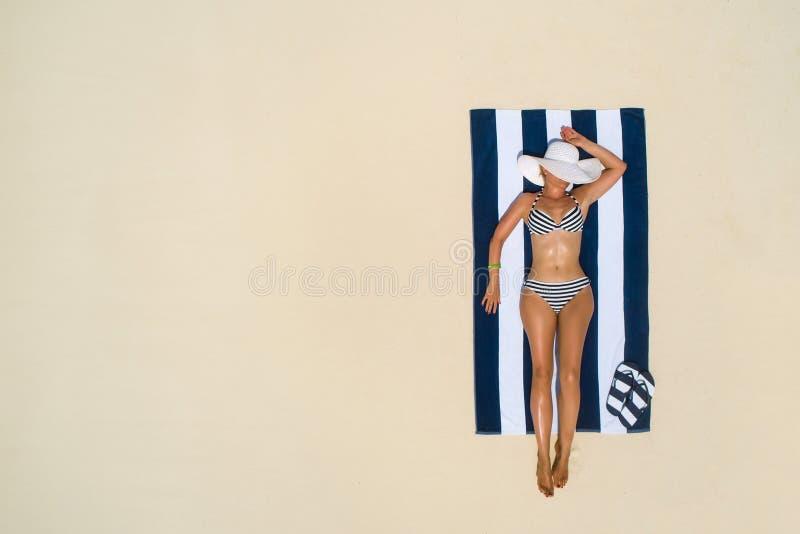 Begrepp för mode för sommarferie - garva den bärande solhatten för flicka på stranden på en vit sand som skjutas från över B?sta  royaltyfri bild