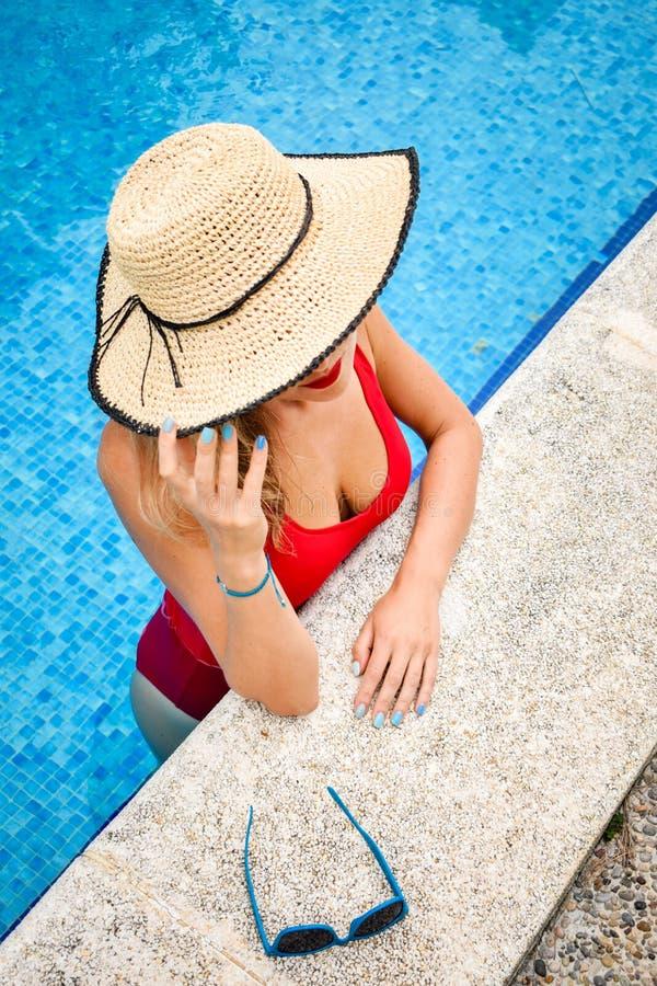 Begrepp för mode för sommarferie - härlig ung kvinna i simbassängen på en solig sommardag royaltyfri fotografi