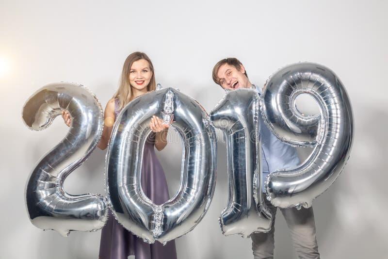 Begrepp för nytt år, beröm- och ferie- roligt förälskelsepar som rymmer tecken 2019 gjort av silverballonger för nytt år på arkivfoton