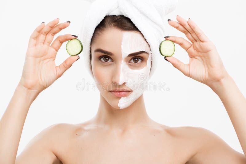 Begrepp för omsorg för skönhetungdomhud - applicerar den härliga Caucasian kvinnan för ståenden den nya gurkan för kräm och för i royaltyfri foto