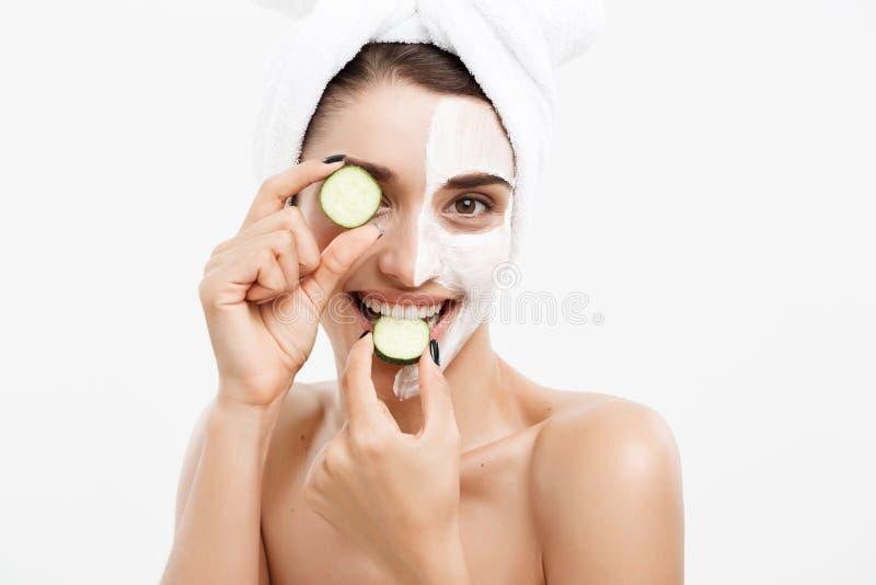 Begrepp för omsorg för skönhetungdomhud - applicerar den härliga Caucasian kvinnan för ståenden den nya gurkan för kräm och för i royaltyfri bild