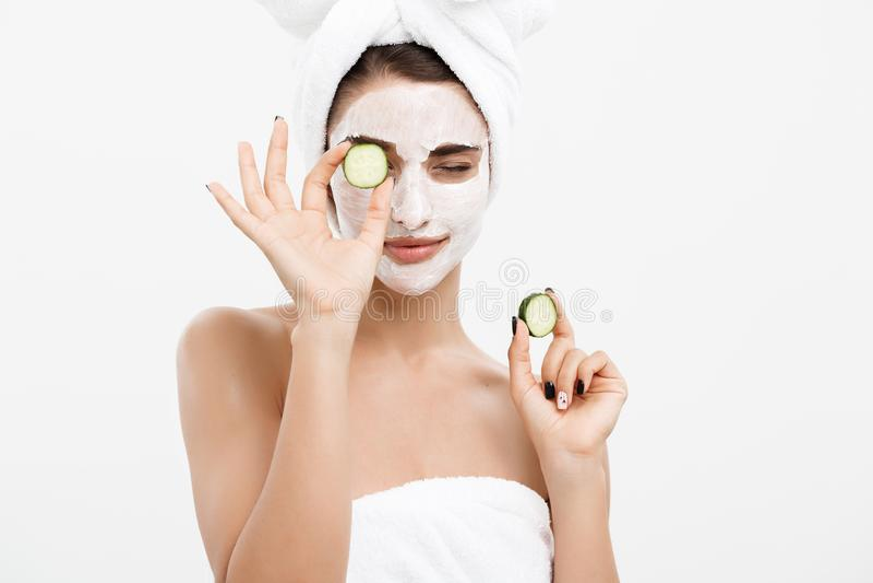 Begrepp för omsorg för skönhetungdomhud - applicerar den härliga Caucasian kvinnan för ståenden den nya gurkan för kräm och för i arkivfoto