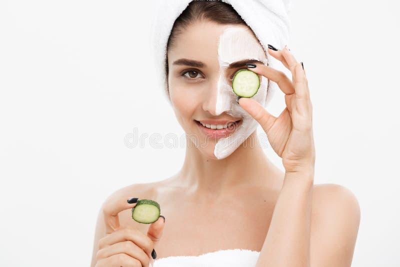 Begrepp för omsorg för skönhetungdomhud - applicerar den härliga Caucasian kvinnan för ståenden den nya gurkan för kräm och för i royaltyfri fotografi