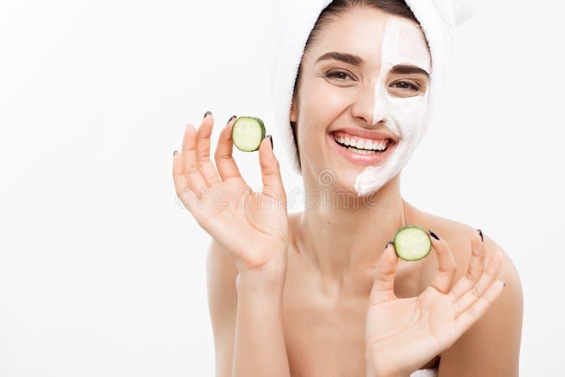 Begrepp för omsorg för skönhetungdomhud - applicerar den härliga Caucasian kvinnan för ståenden den nya gurkan för kräm och för i arkivfoton