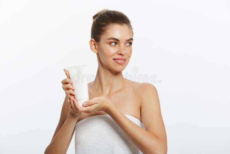 Begrepp för omsorg för skönhetungdomhud - härligt Caucasian innehav för kvinnaframsidastående och framlägga den kräm- rörprodukte royaltyfri bild