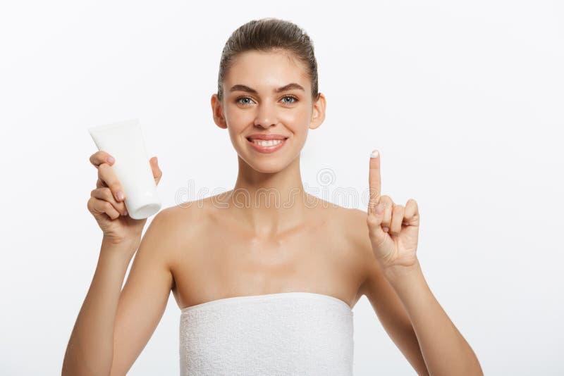 Begrepp för omsorg för skönhetungdomhud - härligt Caucasian innehav för kvinnaframsidastående och framlägga den kräm- rörprodukte royaltyfri fotografi