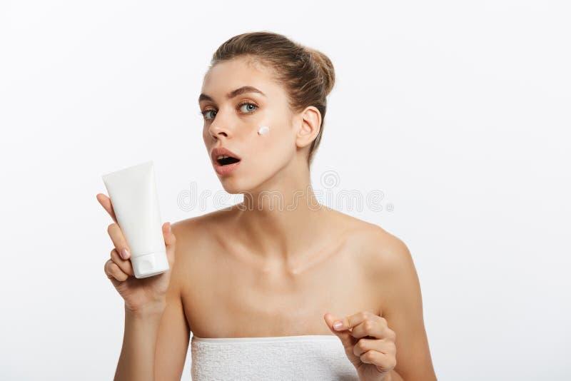 Begrepp för omsorg för skönhetungdomhud - härligt Caucasian innehav för kvinnaframsidastående och framlägga den kräm- rörprodukte royaltyfria bilder