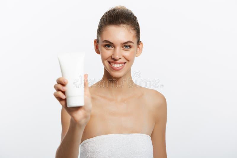 Begrepp för omsorg för skönhetungdomhud - härligt Caucasian innehav för kvinnaframsidastående och framlägga den kräm- rörprodukte arkivfoton