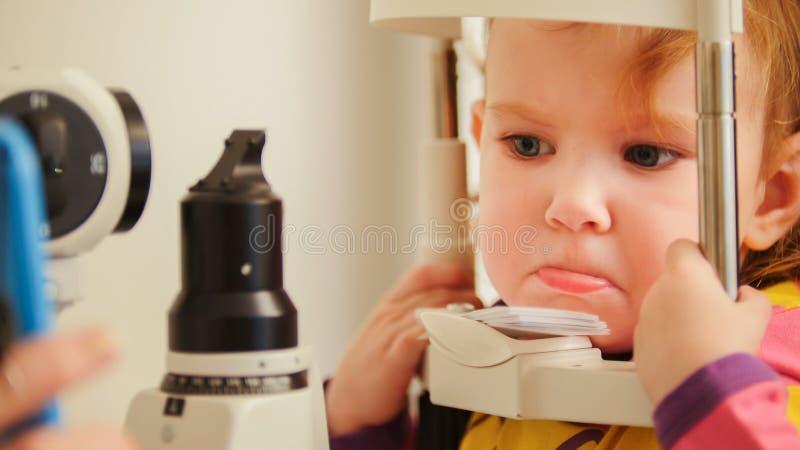 Begrepp för optometry för barn` s - ilsken liten flicka när kontrollsynförmåga i ophthalmological klinik för öga arkivbilder