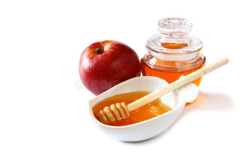 Begrepp för Rosh hashanah (jeweshferie) - honung och rött äpple som isoleras på vit traditionella feriesymboler arkivfoton