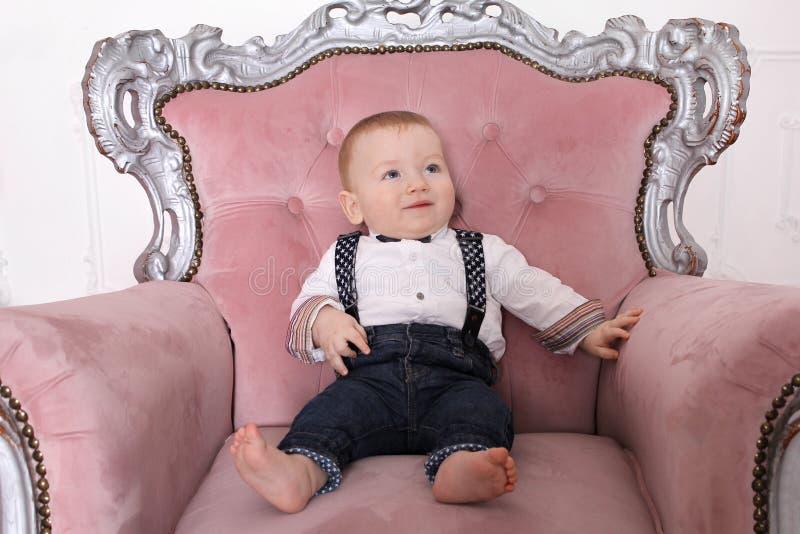 Begrepp för ` s för nytt år för familj Barnpojken sitter i en stol fotografering för bildbyråer