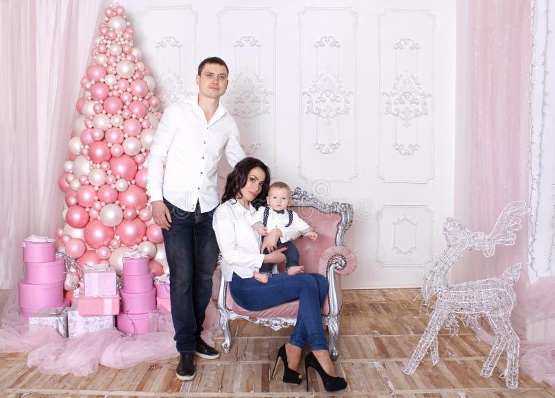 Begrepp för ` s för nytt år för familj Mamman och farsan rymmer deras behandla som ett barn royaltyfri foto