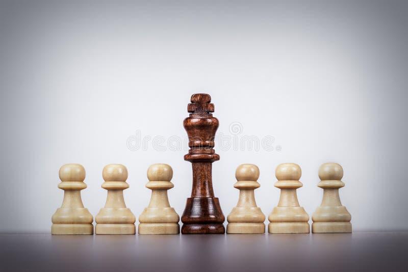Begrepp för schackkonungledarskap över grå bakgrund arkivfoton