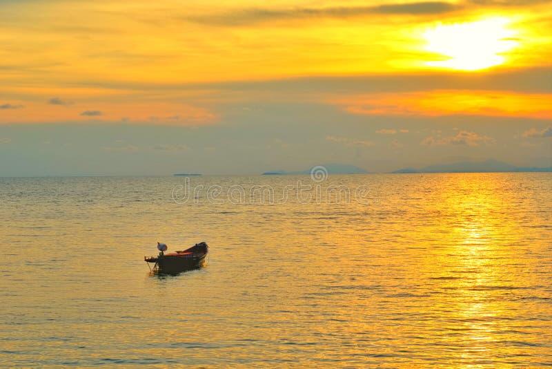Begrepp för semestertid, a-fartyg som går och parkerar i havet med solnedgångtid eller guld- tid och moln royaltyfria foton