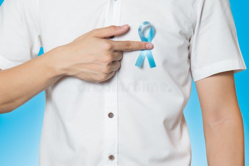 Begrepp för sjukvård för man` s - som är nära upp av den manliga handen som pekar till ljus - strumpebandsorden för prostatacance arkivbilder