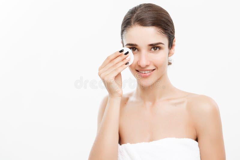 Begrepp för skönhethudomsorg - den härliga kvinnan som gör ren hennes framsida med bomullsbomullstoppen - över vitt bakgrund och  arkivbilder