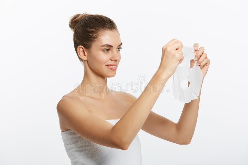 Begrepp för skönhethudomsorg - härlig Caucasian kvinna som applicerar den pappers- arkmaskeringen på hennes framsidavitbakgrund royaltyfri fotografi