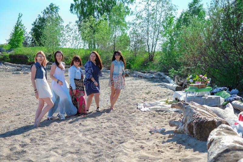 Begrepp för sommarferier - gruppen av att le unga kvinnor vilar på kusten royaltyfri bild