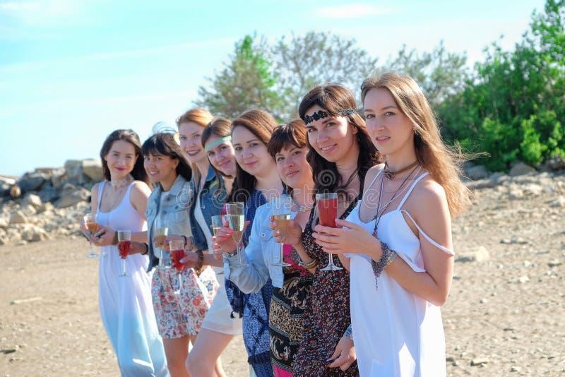Begrepp för sommarferier - gruppen av att le unga kvinnor vilar på kusten arkivbild