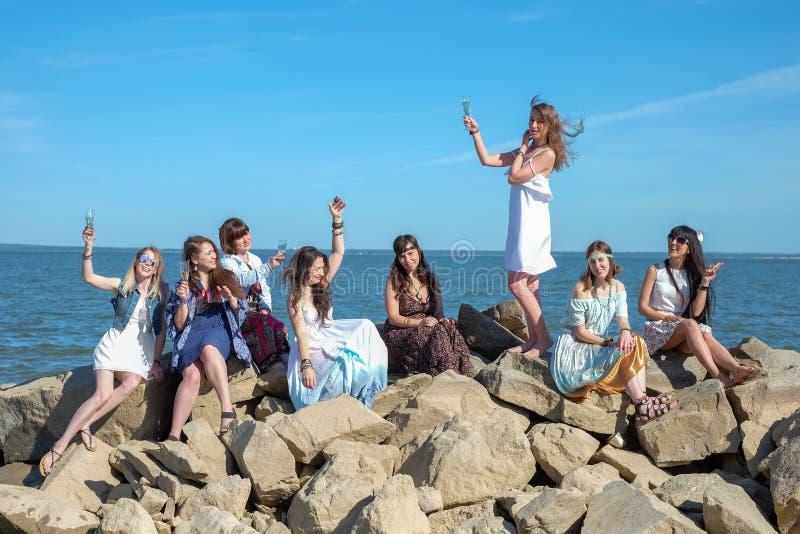 Begrepp för sommarferier - gruppen av att le unga kvinnor vilar på kusten royaltyfri fotografi