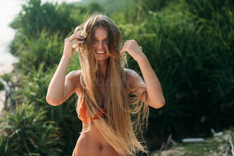 Begrepp för sommarlivsstilsemester Stående av en ung lycklig brunbränd kvinna med tjockt långt blont hår som ler och royaltyfri fotografi