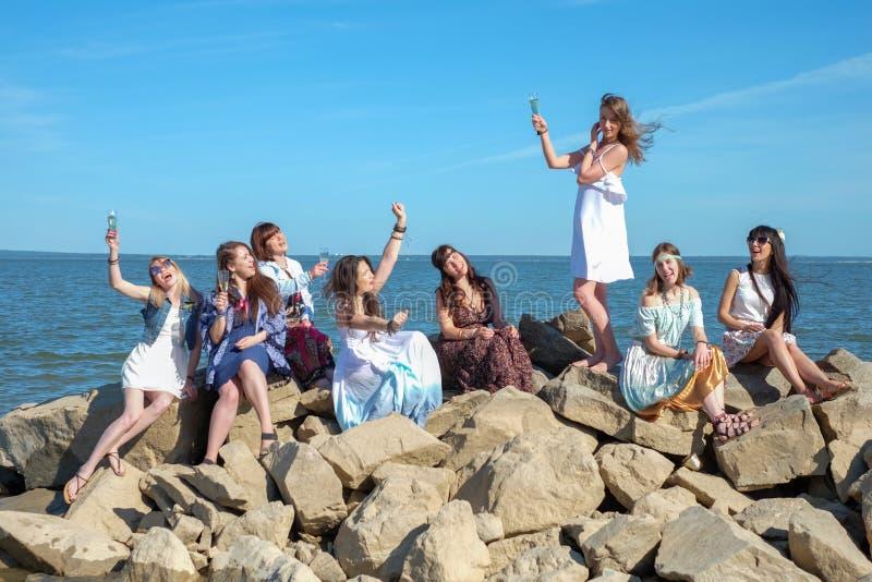 Begrepp för sommarsemester, ferie-, lopp- och folk- grupp av att le unga kvinnor på stranden royaltyfria foton
