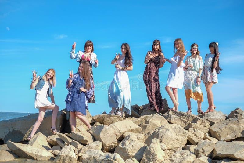 Begrepp för sommarsemester, ferie-, lopp- och folk- grupp av att le unga kvinnor på stranden royaltyfri fotografi