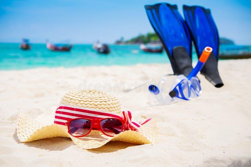 Begrepp för sommarsemester med tillbehör på den sandiga stranden royaltyfri fotografi