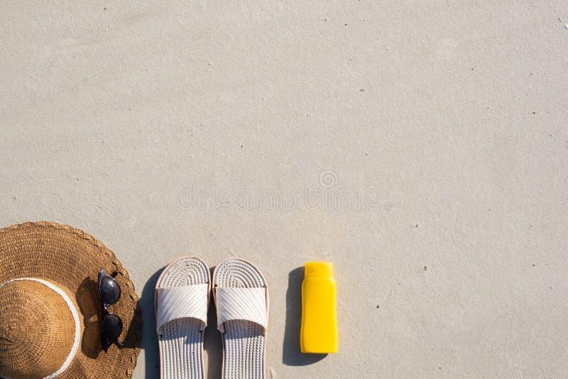 Begrepp för sommarsemester: strandhäftklammermatare, skyddande kräm och en hatt på ren sand royaltyfria bilder