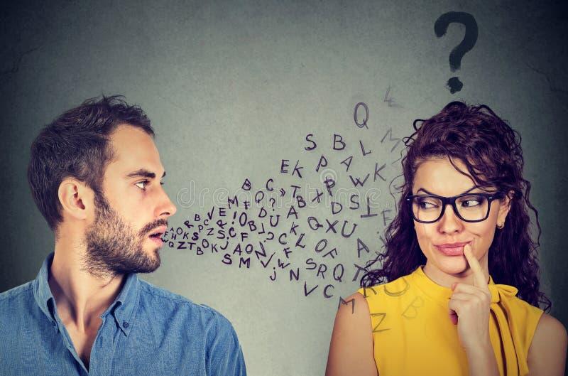 Begrepp för språkbarriär Man samtal till en ung kvinna med frågefläcken arkivfoton