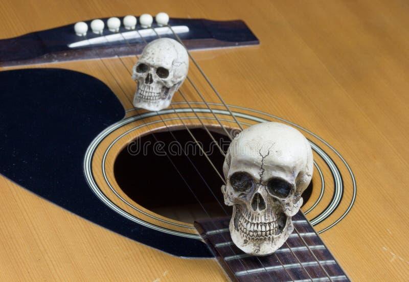 Begrepp för stillebenkonstfotografi med skallen och gitarren arkivfoton