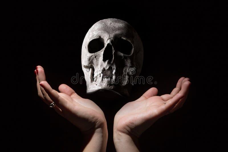 Begrepp för svart magi Mänsklig skalle mellan kvinnahänder på svart bakgrund arkivbild
