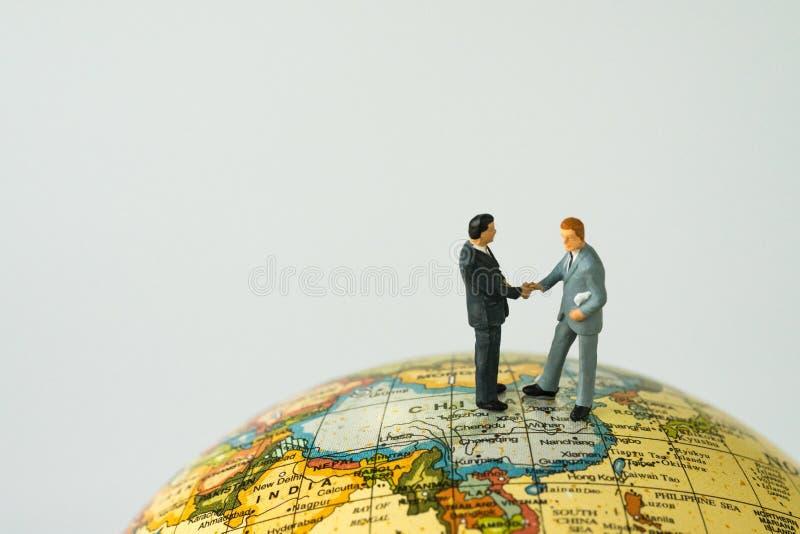 Begrepp för teamwork för skaka för världsledandeöverenskommelsehand med miniatu royaltyfri foto