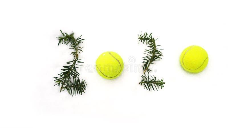Begrepp för tennisjul och för nytt år 2020 med tennisbollar och granfilialer med nummer på vit snö som isoleras arkivbild
