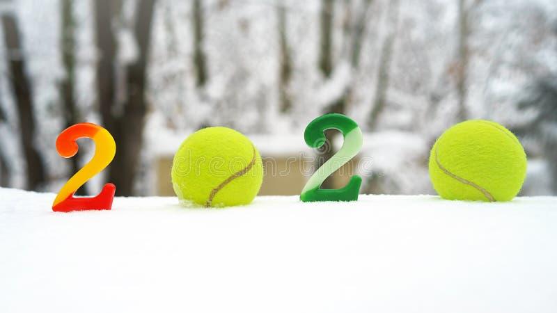 Begrepp för tennisjul och för nytt år 2020 med tennisbollar och stearinljus med nummer på vit snö som isoleras royaltyfria bilder