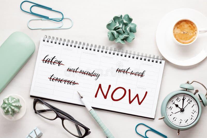 Begrepp för Tid ledning med anmärkningar i veckoorganisatör över skrivbordet med kaffe och ringklockan arkivbild