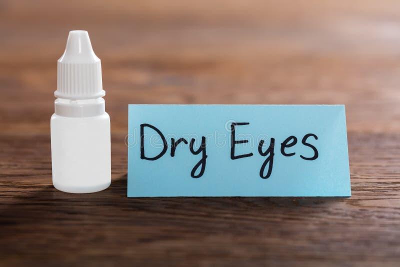 Begrepp för torra ögon på träskrivbordet arkivfoton
