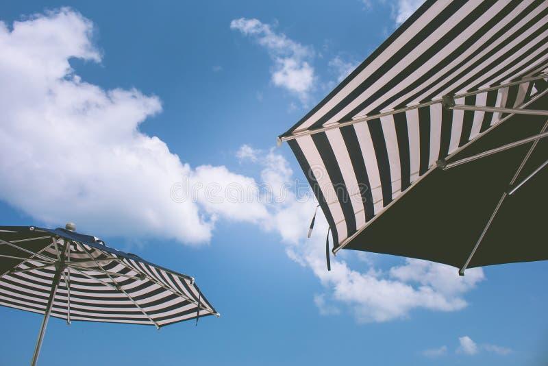 Begrepp för tur för sommarsemester och ferie: Slut upp den svartvita paraplystranden med blå himmel i bakgrunden royaltyfria foton