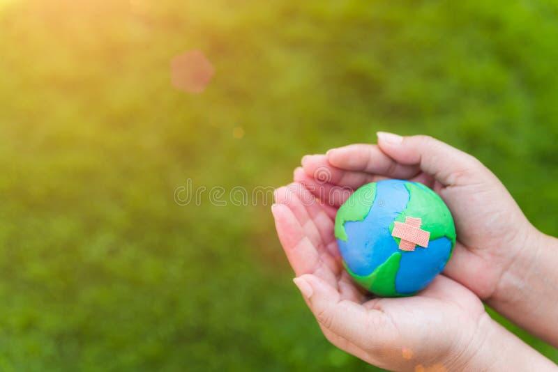 Begrepp för världsjorddag Kvinnahand som rymmer det handgjorda jordklotet arkivbild