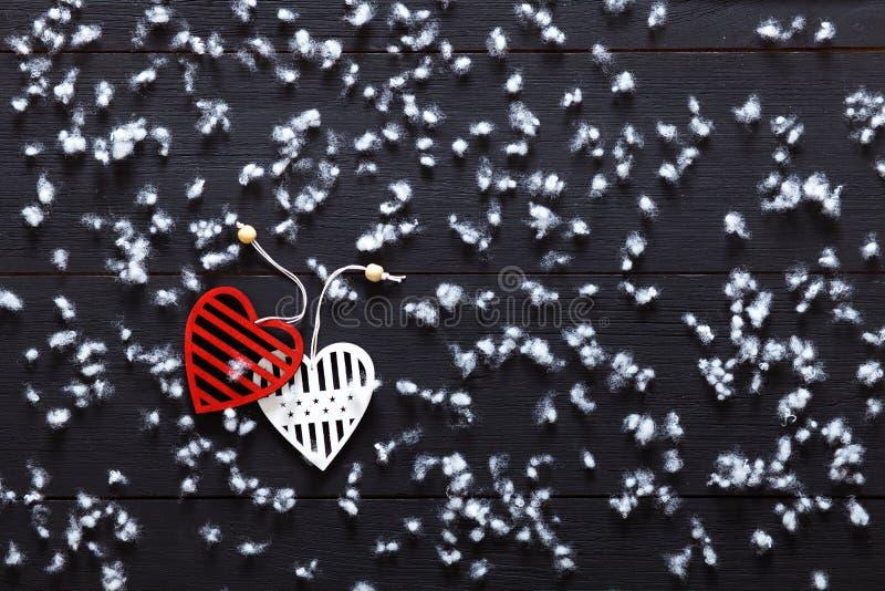 Begrepp för valentindagkort, snöflingor två vita röda hjärtor på den svarta trätabellen som täckas med snö, romantisk feriebakgru arkivbilder