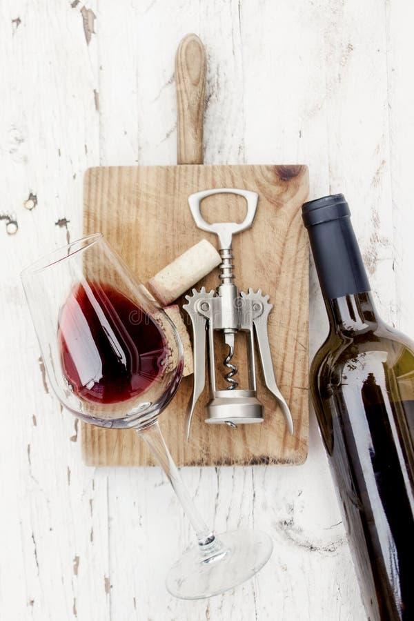 Begrepp för vinavsmakning - flaska av rött vin, exponeringsglas och korkskruvet royaltyfri foto
