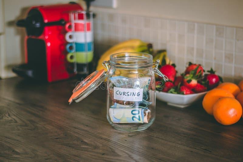 Begrepp: förbanna kruset med pengar inom av den överst av tabellen för kök` s royaltyfri foto