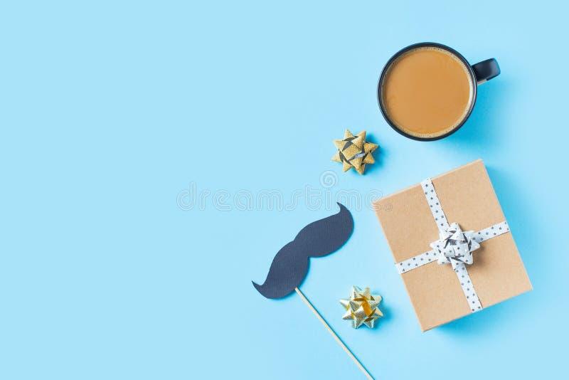 Begrepp f?r faderdag med det g?vaasken, bandet och mustaschen p? bl? bakgrund arkivfoto
